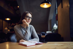 Atractive young girl trying understand bussines strategy of hostel and restraunt. Thoughtful female reader in spectacles sitting with interesting book in empty Royalty Free Stock Image