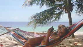 Atractive girl using mobile phone in hammock at the beach near the sea and palm tree. Thailand. HD. Slow motion. Atractive Young girl Using Mobile Phone in stock video