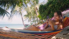 Atractive young happy woman Using Mobile Phone in Hammock at the Beach near the Sea and palm tree. Thailand. HD. Slow. Atractive Young girl Using Mobile Phone in stock video