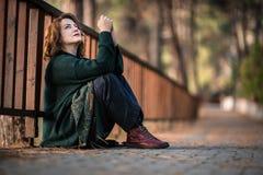 Atractivevrouw door een Houten Omheining in Bos, het Denken en DA stock afbeeldingen