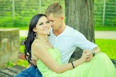 Atractivo el individuo con la muchacha se sienta y abraza en un banco Fotos de archivo