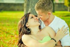 Atractivo el individuo con la muchacha se sienta y abraza en un banco Foto de archivo