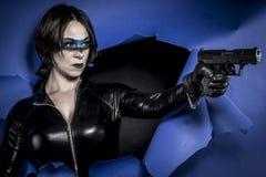 Atractivo, morenita en traje negro del látex con la pistola sobre el PA quebrado foto de archivo