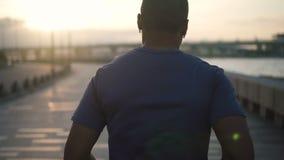 Atractivo ningún atleta sano negro del hombre joven de la cara agotado y funcionamiento con la acera en el bavkground que escucha metrajes