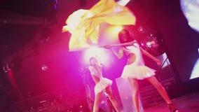 Atractivo vaya van muchacha en las banderas blancas de la onda de los trajes en partido en club nocturno en etapa luces almacen de video