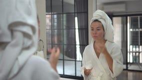 Atrakcyjna ładna młoda kobieta stoi blisko lustra w łazience, bierze opiekę jej skóra, stawia śmietankę na jej twarzy, zbiory