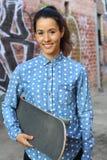 Atrakcyjna żeńska łyżwiarka trzyma jej deskę w łyżwowy alleyway ono uśmiecha się Zdjęcia Stock