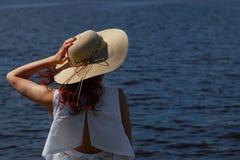 Atrakcyjna żeńska osoba w biel sukni mienia splendoru kapeluszu outdoors na rzecznym brzeg, tylny widok, głęboka błękitne wody na Zdjęcie Stock