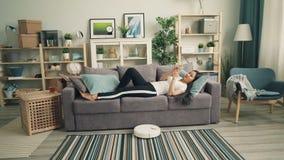 Atrakcyjna Azjatycka dziewczyna używa smartphone i relaksuje na kanapie podczas gdy mechaniczny próżniowy czysty czyści podłogi w zbiory wideo