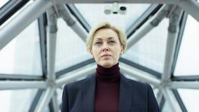 Atrakcyjna biznesmenka patrzÄ…ca na kamerÄ™ na zewnÄ…trz podczas pracy w nowoczesnym centrum biznesowym. Ona ma na sobie uroczysto zdjęcie wideo