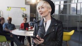 Atrakcyjna biznesowa kobieta pracuje na smartphone z grupą młodzi ludzie biznesu na tle zdjęcie wideo