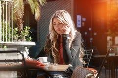 Atrakcyjna biznesowa kobieta pracuje w kawiarni, opowiada na phon obraz royalty free