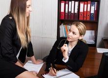 Atrakcyjna biznesowa kobieta pracuje z dokumentami w biurze kobieta w garnituru obsiadaniu przy znakiem i stołem zdjęcie stock
