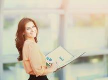 Atrakcyjna biznesowa kobieta trzyma falcówkę z mapami i diagramami w biurze obraz royalty free