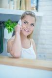Atrakcyjna blond kobieta opowiada na jej wiszącej ozdobie Fotografia Stock