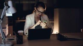 Atrakcyjna blondynka używa smartphone texting póżno i uśmiechnięty obsiadanie w biurowy samotnym przy nocą Nowożytni gadżety, moc zbiory