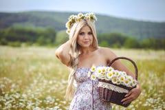 Atrakcyjna blondynka w chamomile polu. Młoda kobieta w wianku fotografia stock