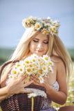 Atrakcyjna blondynka w chamomile polu. Młoda kobieta w wianku zdjęcie stock