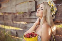 Atrakcyjna blondynka w chamomile polu. Młoda kobieta w wianku zdjęcia stock