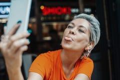 Atrakcyjna blondynki dziewczyna w pomarańczowej koszulce robi selfie przy kawiarnią obraz stock