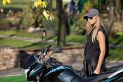 Atrakcyjna blondynki kobieta blisko motocyklu obraz stock