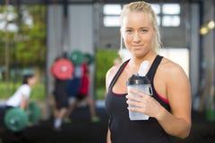 Atrakcyjna blondynki kobieta odpoczywa przy sprawności fizycznej gym zdjęcia stock