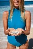 Atrakcyjna blondynki kobieta w błękitnym swimwear z seashells w rękach na linii brzegowej Obrazy Stock