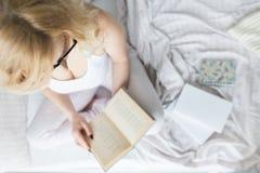 Atrakcyjna blondynki kobieta w szk?ach z czarnym obr?czem siedzi na kraw?dzi ? obrazy royalty free