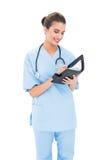 Atrakcyjna brown z włosami pielęgniarka w błękicie szoruje wypełniać agendę Obrazy Stock
