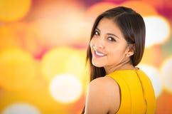 Atrakcyjna brunetka jest ubranym kolor żółty suknię pozuje naturalnie i ono uśmiecha się piękny kamera z rozmyty kolorowym Zdjęcie Royalty Free