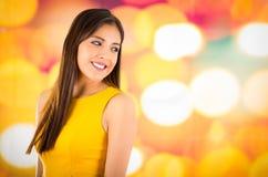 Atrakcyjna brunetka jest ubranym kolor żółty suknię pozuje naturalnie i ono uśmiecha się piękny kamera z rozmyty kolorowym Fotografia Stock