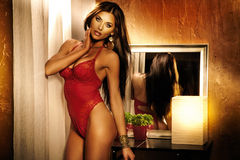 Atrakcyjna brunetki dama pozuje w czerwonej bieliźnie, patrzeje przychodził Fotografia Stock
