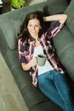 Atrakcyjna brunetki dziewczyna odpoczywa na kanapie zdjęcia stock