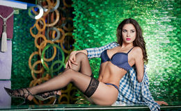 Atrakcyjna brunetki kobieta kłaść na barze w klubie nocnym z długimi nogami w bieliźnie i czarnych pończochach wspaniały target84 Zdjęcia Stock