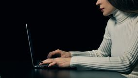 Atrakcyjna brunetki kobieta pisać na maszynie na jej przenośnym komputerze przeciw ciemnemu tłu 4K wideo zbiory wideo