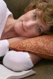 Atrakcyjna brunetki kobieta relaksuje na leżance z książką Zdjęcia Stock