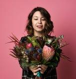 Atrakcyjna brunetki kobieta wewn?trz w ciemnym w kratk? smokingowym mienie bukiecie kwiaty przed ona obraz stock