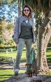 Atrakcyjna brunetki kobieta z miniaturowym jamnika psem Obraz Royalty Free