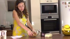 Atrakcyjna brunetki młoda kobieta robi deserowi w domu 4K steadicam strzał zdjęcie wideo