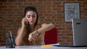 Atrakcyjna caucasian kobieta opowiada nad telefonem i sprawdza czas na jej zegarku podczas gdy siedzący w ceglanym studiu przy on zbiory