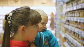 Atrakcyjna caucasian kobieta wybiera dziecięcego jedzenie w supermarkecie trzyma jej dziecka w rękach Zakończenie strzelający mam zbiory