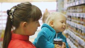 Atrakcyjna caucasian kobieta wybiera dziecięcego jedzenie w supermarketa mienia dziecku w rękach Zakończenie strzelający mama i d zbiory