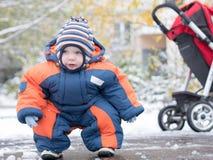 Atrakcyjna chłopiec bawić się z pierwszy śniegiem Uśmiecha się bałwanu i patrzeje Gęstego pomarańcze kombinezonu jaskrawy pasiast Zdjęcia Royalty Free