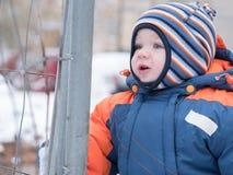 Atrakcyjna chłopiec bawić się z pierwszy śniegiem Uśmiecha się bałwanu i patrzeje Gęstego pomarańcze kombinezonu jaskrawy pasiast Zdjęcie Stock