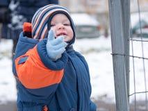 Atrakcyjna chłopiec bawić się z pierwszy śniegiem Uśmiecha się bałwanu i patrzeje Gęstego pomarańcze kombinezonu jaskrawy pasiast Fotografia Royalty Free
