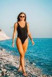 Atrakcyjna dębna kobieta w czarnym swimsuit na plaży Fotografia Royalty Free