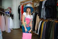 Atrakcyjna dama w błękit być wypełnionym czymś kapeluszu robi zakupom na odzież sklepu tle Sprzedaży i mody pojęcie Zdjęcia Stock