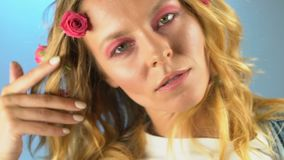 Atrakcyjna dama z małymi różowymi różami w jej włosy pozuje kamera, zwolnione tempo zbiory