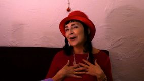 Atrakcyjna dorosła kobieta w czerwieni ubraniach i czerwonym kapeluszu jest zabawy tanem i zabawy śpiewem zdjęcie wideo