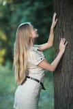 Atrakcyjna dziewczyna dotyka dużego drzewa w parku i patrzeje kamera Fotografia Stock